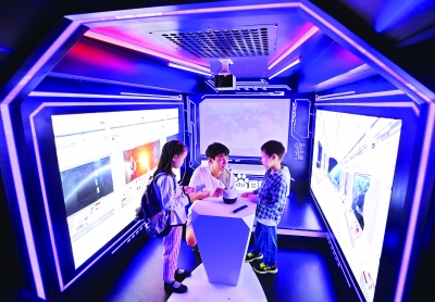 """""""科普大巴""""内,两位小朋友与智能机器人对话    记者郭良朔 摄"""