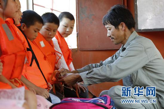 曹道国帮渡船上的孩子系救生衣 新华社记者 杨波 摄