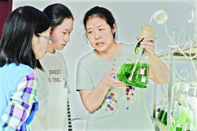 实验室内,中科院武汉水生所胡春香研究员查看学生韩迎春和李琪培养的荒漠藻的长势,并给出指导