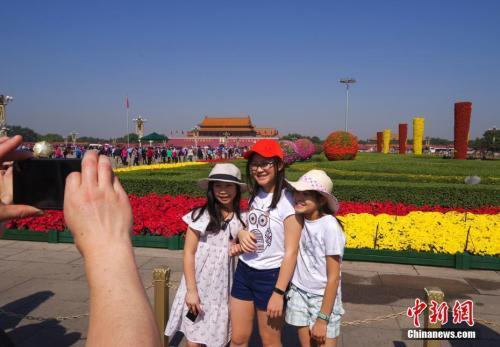 9月29日,三位小游客在北京天安门广场国庆花坛前留影。中新社记者 贾天勇 摄