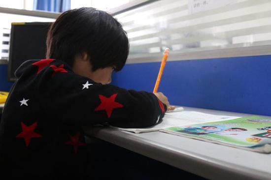 骆红玖值班时,女儿微微独自写作业。