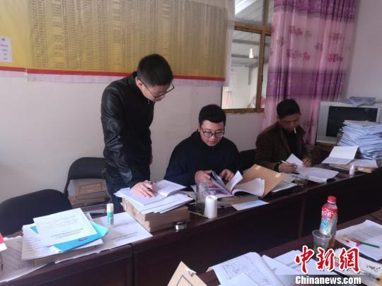 """""""特派村官""""白书瀚(左一)学习整理扶贫档案 兴宣 摄"""