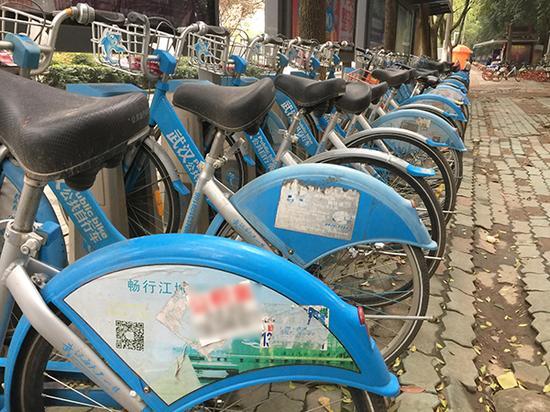 华中科技大学门口,武汉公共自行车上被贴满小广告。