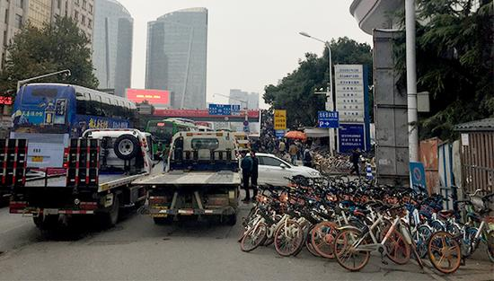 两辆拖车正准备将共享单车拖走。