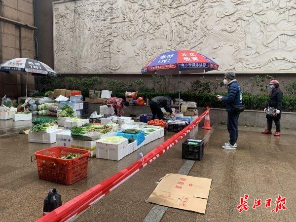 28日上午8点50分,华清园居民冒着零星小雨在临时菜场买菜。 记者汪峥摄
