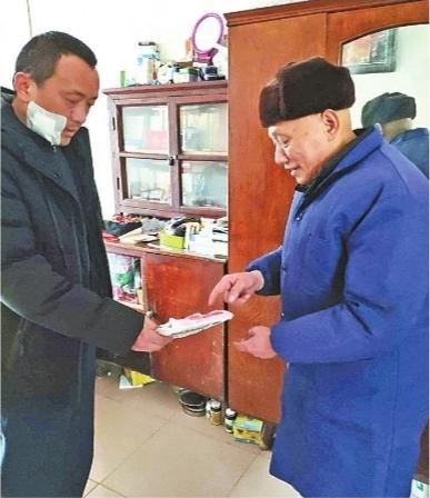 赵明山(右)让儿子协助自己做好管账工作 通讯员陶火应 摄