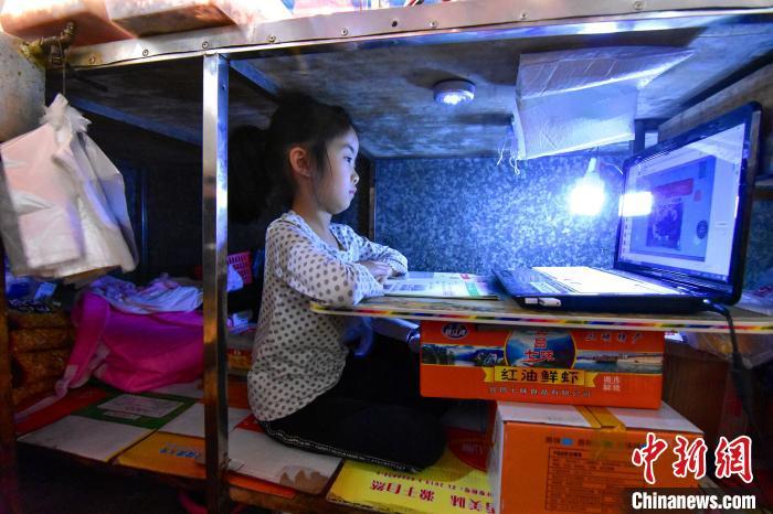 7岁的柯恩雅在卤菜铺案板下上网课 杨威 摄