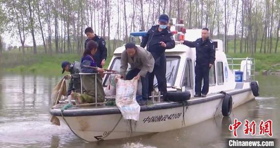 图为执法人员将螺蛳放归河中。 宋博 摄