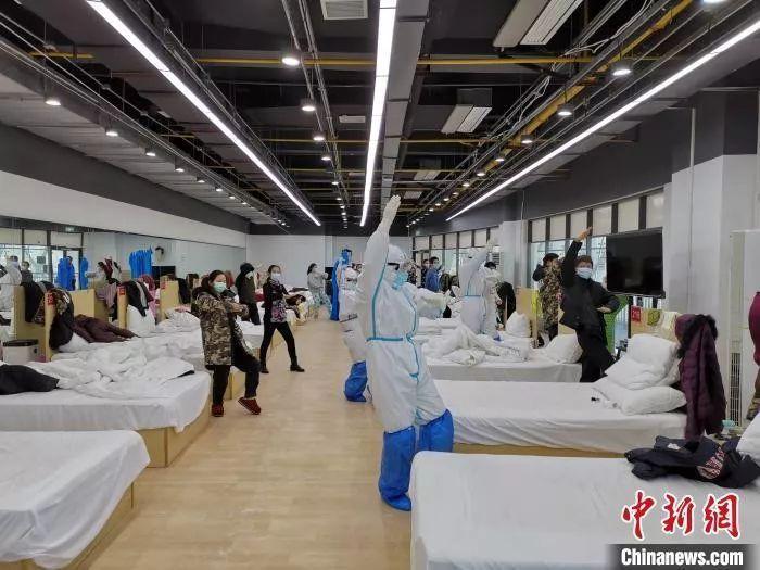 """17日,在武汉大花山方舱医院,医护人员带领一批患者积极""""解锁""""太极拳技能。 张明 摄"""