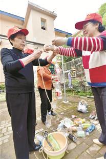 图为居民们改造废弃塑料瓶