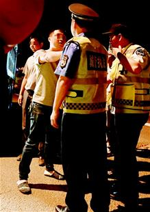 图为:城管队员在执法时,受到不明身份人员的阻挠