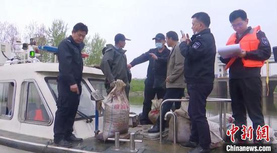 图为执法人员发现汉川市经济开发区神灵口村附近水域有人捕捞螺蛳。 宋博 摄