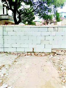 图为:董婆婆家门口被建筑垃圾堵住,还被筑起了一道围墙