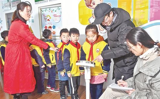 图为:吴家山四小足球队的学生们在测量体重 楚天都市报记者黄士峰摄