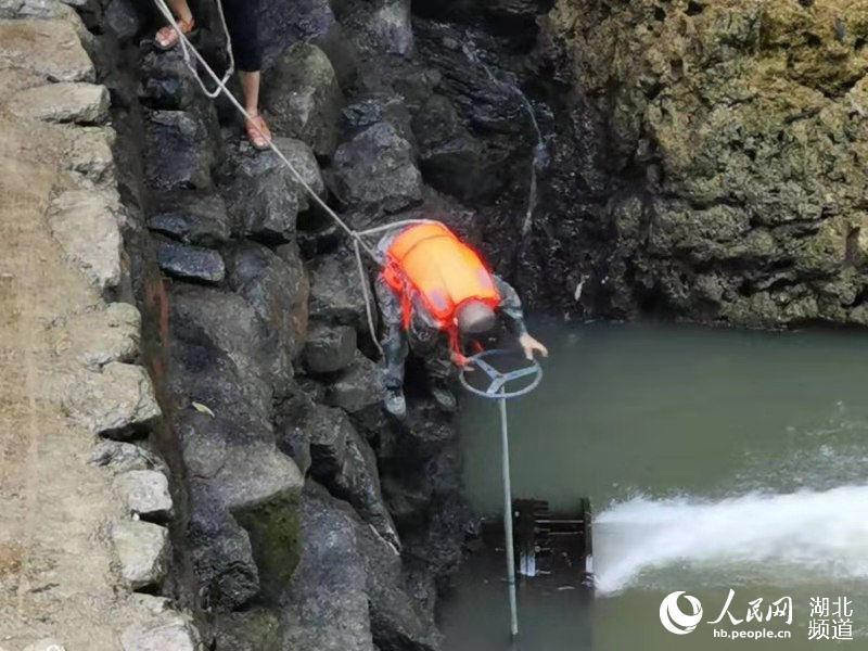 民兵应急队员冒着危险组织深水潭排水,进一步摸排深水潭水底情况。(杨驹 摄)