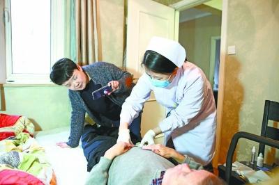 为患者进行造口护理,家属在一旁录像、观摩