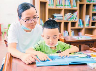 在内蒙古自治区呼和浩特市玉泉区图书馆,小朋友在家长陪伴下读书。   丁根厚摄(人民视觉)