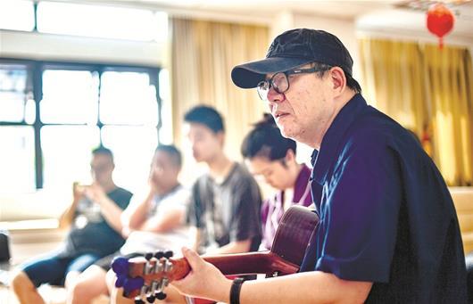图为:冯翔在给患者做音乐治疗