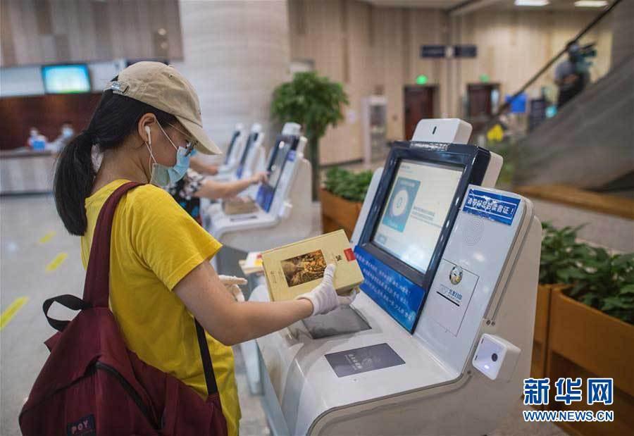 6月14日,在湖北省图书馆,市民归还借阅的书籍。新华社记者肖艺九摄