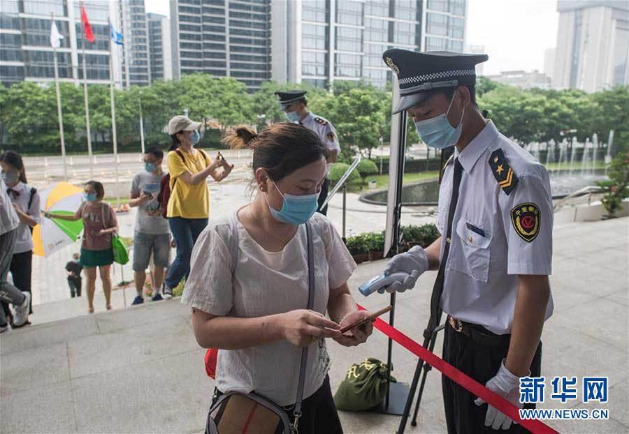 6月14日,市民经过体温检测、扫健康码后进入湖北省图书馆。新华社记者肖艺九摄