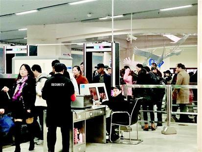 图为:汉口火车站地铁安检口排起长队