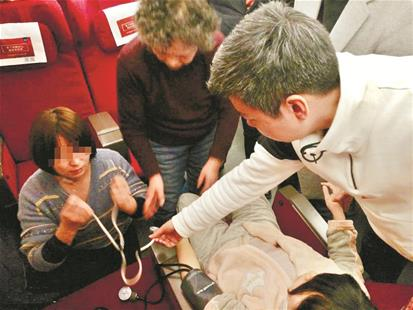 图为:侯远兰(上)和两名医生共同救人