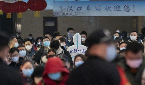 汉口火车站出站通道中,警务人员身穿防护服维持秩序。新京报记者陶冉摄