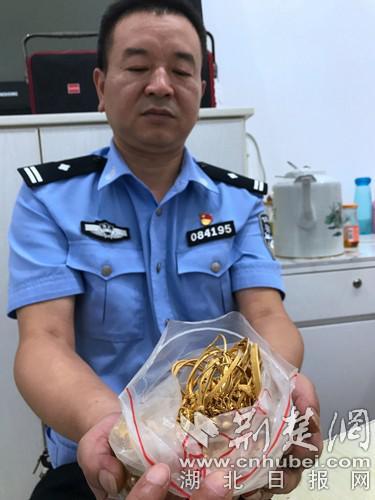 民警展示皮包内的部分金饰。通讯员 卫冬 摄