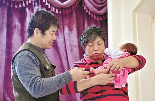 图为:武汉59岁的郭女士上月生下试管宝宝,成为我省目前最高龄产妇。图为夫妇俩在悉心照顾小毛毛。 楚天都市报记者王永胜摄