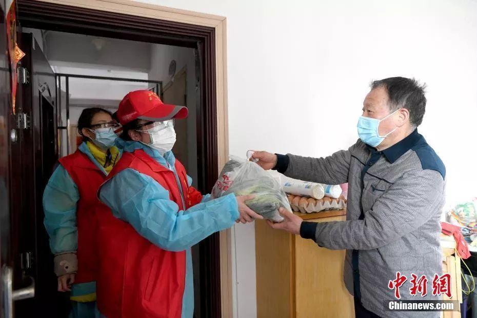 图为武汉市青山区红钢城街道青扬社区工作人员为居民送菜上门。 安源 摄