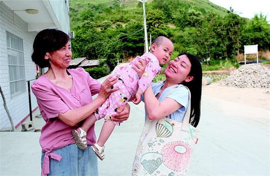 图为:忙碌了一天,王庆年回到住地,从妈妈手里接过孩子。(湖北日报全媒记者 刘汉泽 通讯员 张启国 摄)