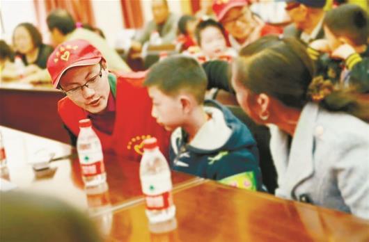 图为吴春友(左)生前参加志愿服务