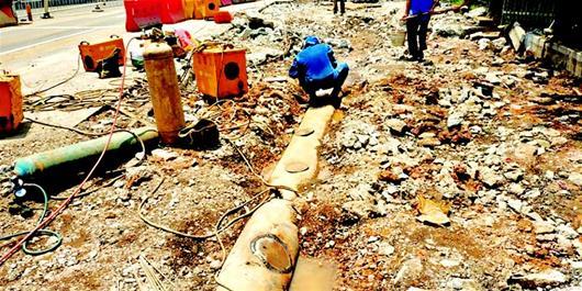 图为抢修工人修补破损管道