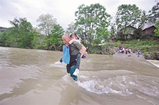 图为:侯长辉在背孩子过河通讯员彭涛摄