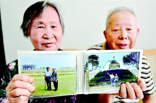 图为两位老人在旅途中拍了很多纪念照