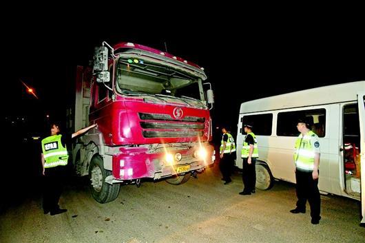 图为:5月14日晚,城管执法车将一辆渣土车拦停