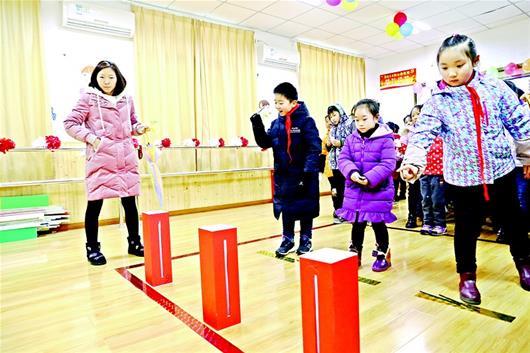 图为:南望山小学的学生们在体验投壶游戏