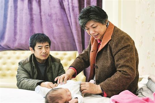 图为:郭女士和丈夫陈先生悉心照料孩子