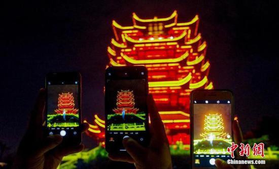10月1日晚,武汉城市地标黄鹤楼正式开放夜间体验,《夜上黄鹤楼》行浸式光影演艺体验版正式亮相。游客与市民漫步园区内步道,拍照打卡,参与互动游戏。在行浸式的体验中穿行在一幅幅光影的历史画卷中,观看黄鹤仙子归去来兮的故事,品味黄鹤楼的前生今世。图为游客们用手机拍下黄鹤楼夜景。中新社记者 张畅 摄