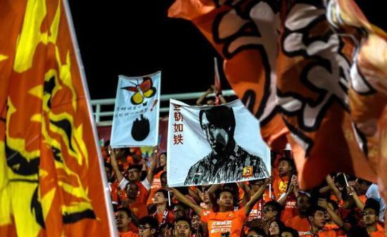 球迷高举李铁画像海报。