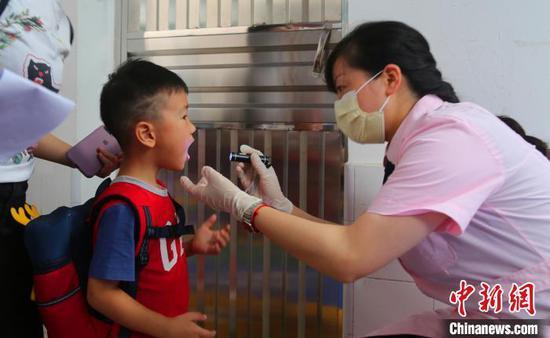 校医对入园的孩子进行身体检查 吴宏福 摄