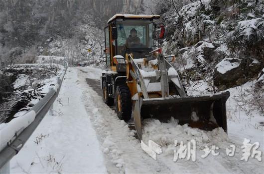 覃俊芳驾驶自家铲车在马鞍山村的山路上铲雪。 通讯员 张晓灵 摄