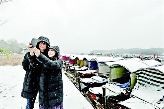 图为:游客在东湖绿道的美丽雪景中自拍