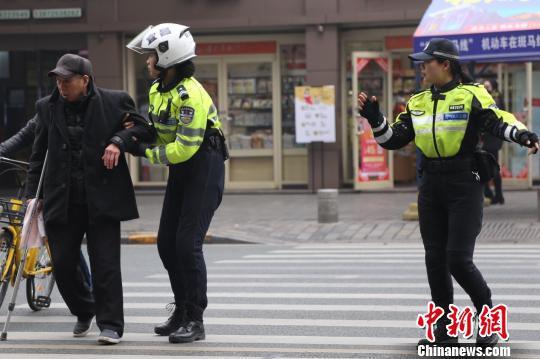 两名女警帮助行动不便老人过马路 宜昌交警供图