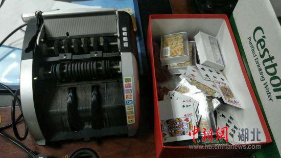 湖北仙桃警方在一居民小区捣毁一个聚众赌博窝点,现场摆放验钞机进行赌博活动。
