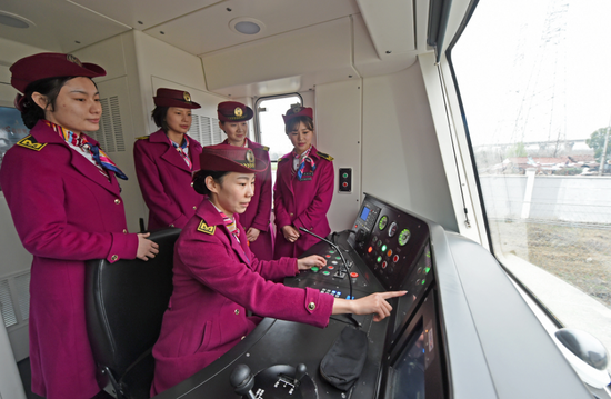 3月6日,驾驶舱内吴亚(中)与同事交流业务。(湖北日报全媒记者倪娜)