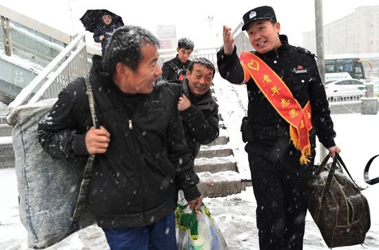 1月3日,湖北省襄阳市,襄阳车站派出所与车站职工组成的青年志愿者服务小分队帮助赶车的旅客。当日,湖北省多地迎来新年的第一场雪。贺瑞明/摄