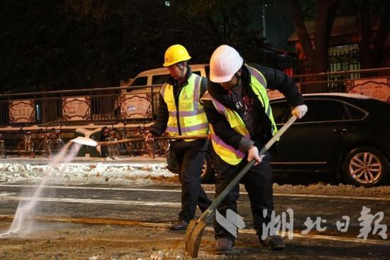 建设者们雪夜上街铲雪保畅通。
