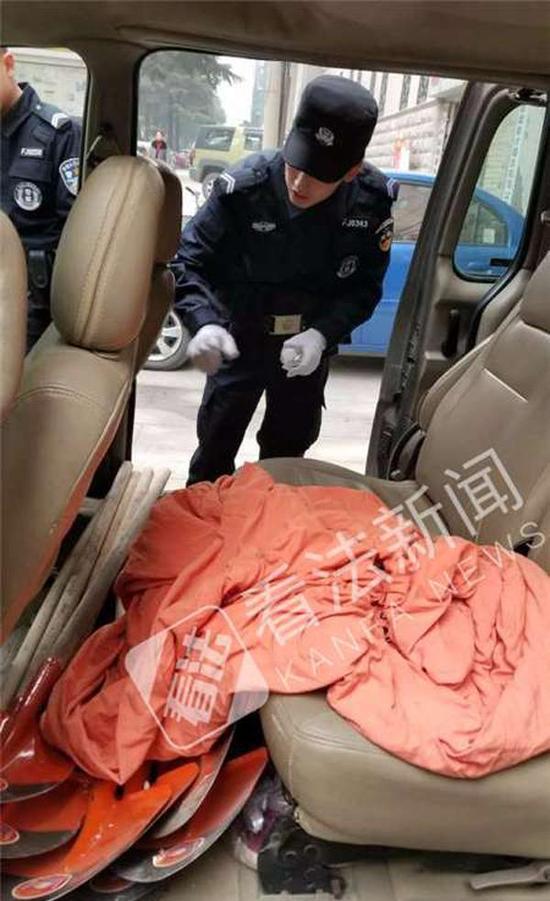 民警检查犯罪嫌疑人车内情况,里面有大量铁锹和布袋等工具。