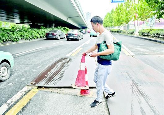 图为:有市民拿来锥筒提醒过路车辆